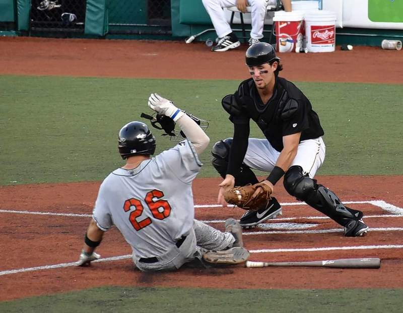 SI Miners catcher Andy Cosgrove waits to apply a tag to Joliet baserunner Peyton Isaacson in Saturday night's home game with the Slammers. Isaacson tried to score from second on a single to right field, but fell victim to the arm of Jimenez.