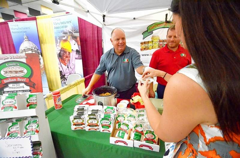 Chris Gualdoni (left) owner of Louie's Seasoning, is shown here with his son, Louis, at the Southern Illinois Made Expo Saturday interacting with customers.