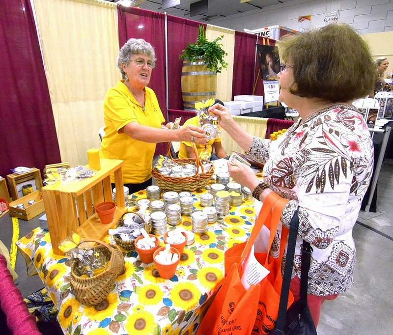 Debbie McVey, with D & M Honey Farm of Carrier Mills, sells some honey to a customer Saturday at the expo.