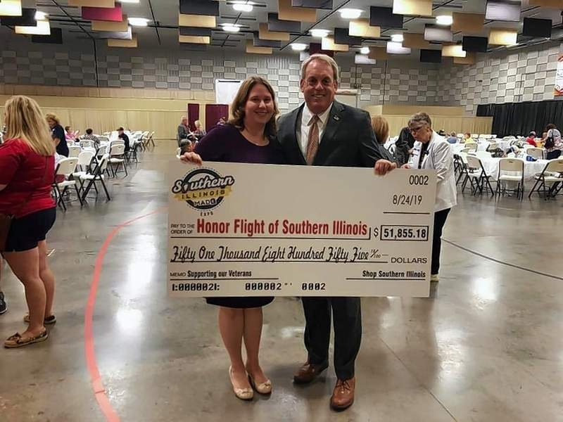 """Marion Chamber of Commerce Executive Director Karen Mullins and Sen. Dale Fowler hold the donation """"check"""" presented to the Honor Flight of the Southern Illinois on Saturday."""