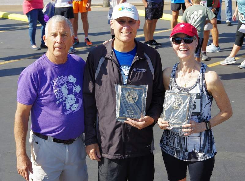 Tom Champion of Salem and Wendy Santi of Toronto, Ontario, get their competitive walk awards from Race Director Bob Platt, left.
