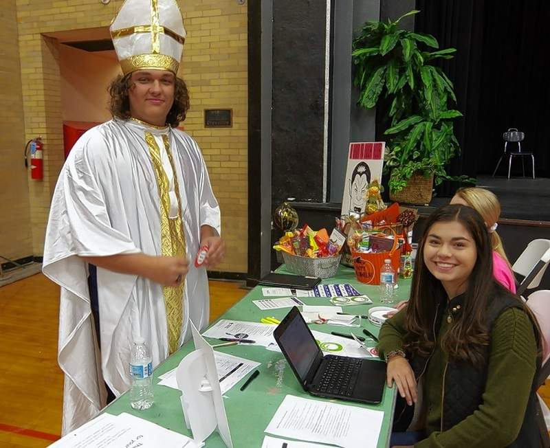 Chester High School senior Wes Carpenter, dressed for Halloween as the Pope, registers to donate blood with fellow CHS senior Amira Al-Jassim, a member of the CHS Student Council.