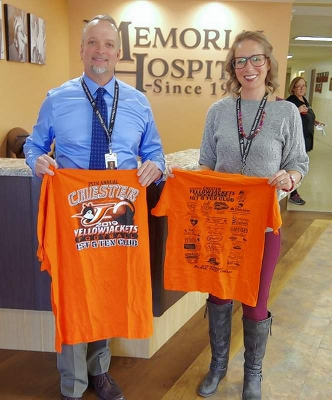 Memorial Hospital CEO Brett Bollmann and Community Relations/Marketing Manager Mariah Bargman hold up the 2019 1st and Ten shirts. Memorial Hospital has joined the team of sponsors for the T-shirts; the sponsors are listed on the back.