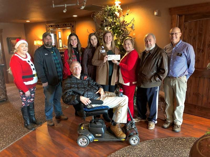 """From left, Vivian Beasley, Brad Elders, Kelcey Keith, Jocelyn Popit, Helen Blackburn, Cynde Bunch, Dave Bunch, Ryan Phelps and Brad Friend (seated) gathered near one of the many Christmas trees at Walker's Bluff Wednesday morning as Dave and Cynde presented a check for $1,506 to Centerstone, one of five area organizations that benefit from WB's """"Wine for a Cause"""" program."""