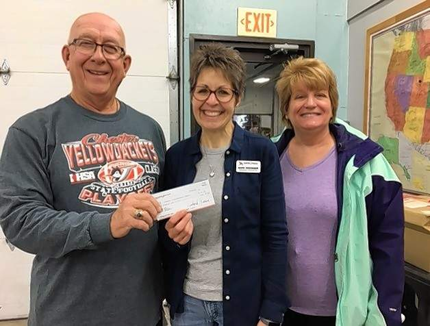 Jim Beers, president of the Methodist Men's Group at First United Methodist Church in Chester, presents a check for $300 from the Methodist Men to Barb Hedinger, far right, missionary coordinator at the Midwest Distribution Center in Springfield. The donation will help with flood relief and other disaster relief. With Beers is his wife, Vicky.