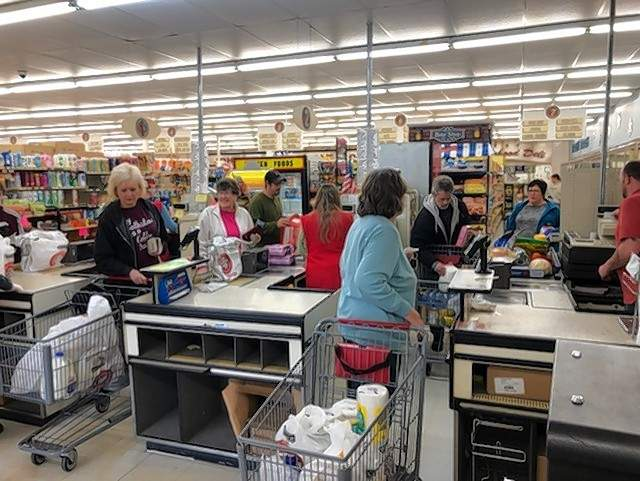 """All checkout lanes were filled with customers at the Johnston City Food Shop on Friday as news of the """"shelter in place"""" order from Gov. J.B. Pritzker filtered through the state."""