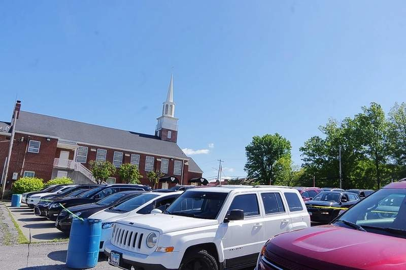 Cars line up on the parking lot of the First Baptist Church in Chester as directed by parking attendants.