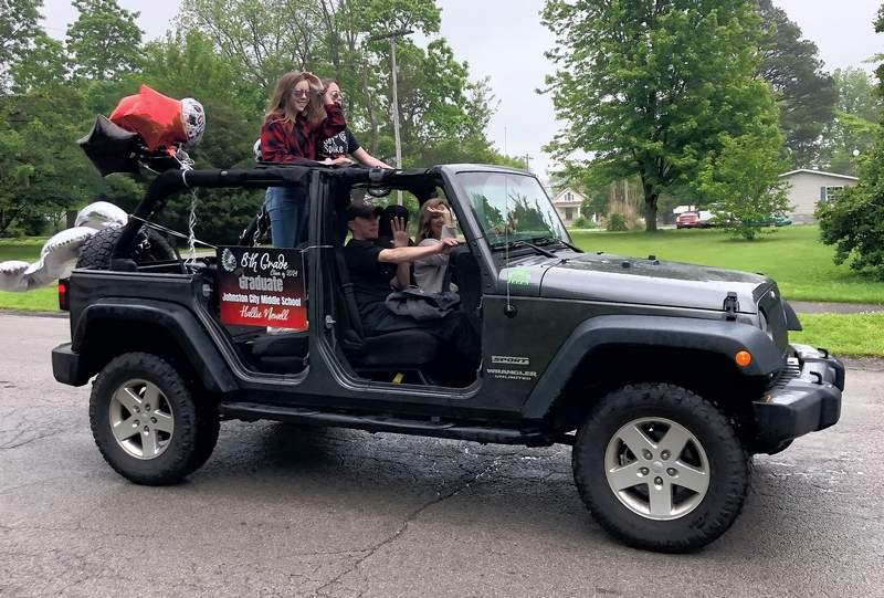 "A little drizzle didn't stop the fun for twins Hallie and Hope Newell, as their parents, Julie and Sean, drove them in the Johnston City Middle School promotion parade Wednesday evening. With the social distancing measures in place, school officials decided to host the ""drive through"" celebration for the school's annual promotion ceremony."