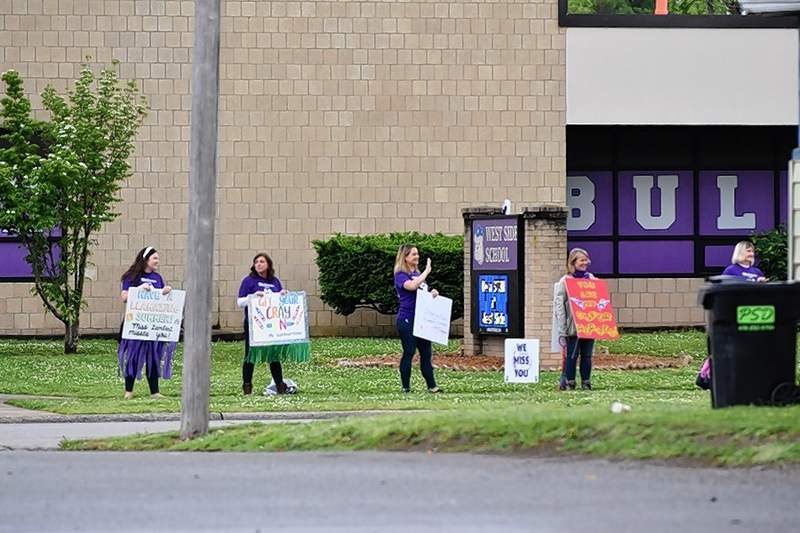 ABOVE: Teachers at West Side School gather -- while still observing social distancing -- to cheer for students at the drive-by Summer Send-Off. Parades have become more and more popular as a way to celebrate the end of school during the coronavirus pandemic.LEFT: Teachers at East Side School cheer as students are driven by. There also will be some sort of a graduation for Harrisburg High School Class of 2020, Unit 3 Superintendent Mike Gauch assured students and parents. In the meantime, however, there will be a parade for seniors at 6 tonight along the Homecoming route.