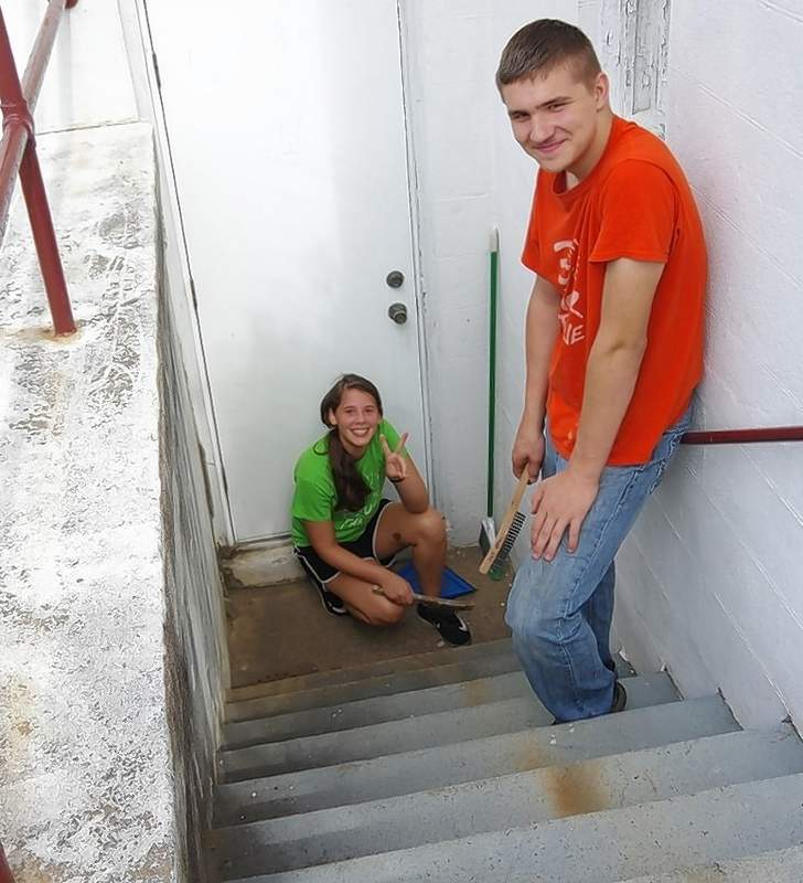 Trinity Brown and Cameron Gasser scrape paint on the staircase leading into the Methodist Church's former fellowship hall.