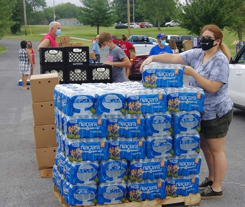 """Hannah Miller of Chester volunteers at the mobile market with the Grace Church Youth Group in what was her final youth group activity as she has now """"aged-out,"""" having completed her first year of college at SWIC. In the background is Drew Coleman distributing cases of milk."""