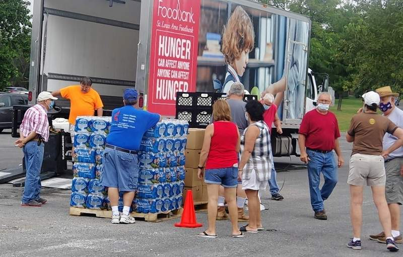 Volunteers unload food off the St. Louis Area Food Bank truck in the morning, prior to opening up the market.