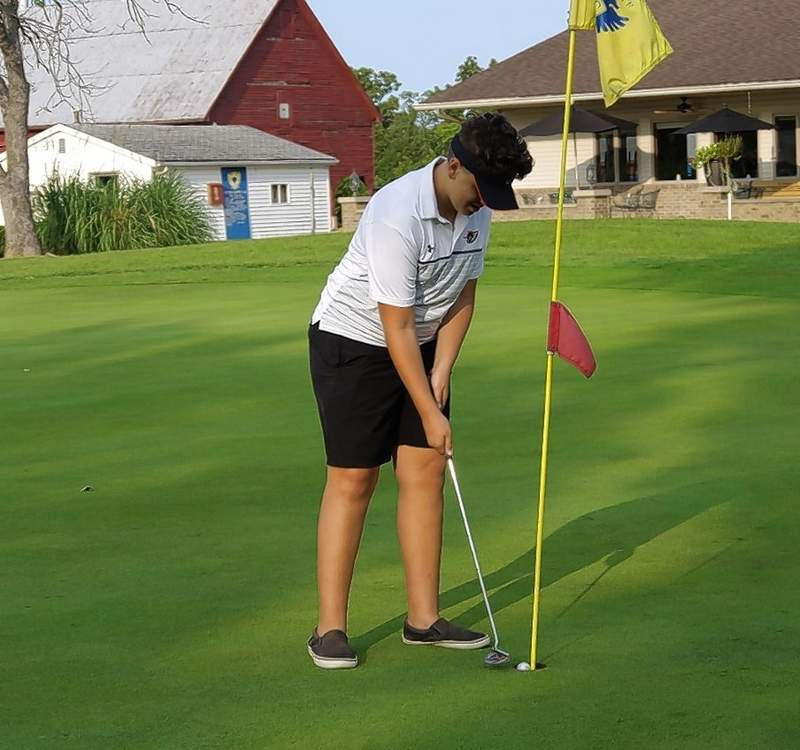 Freshman Isaiah Ferrell putts on hole 9 as the Yellow Jackets host the Freeburg Midgets at the Chester Country Club.