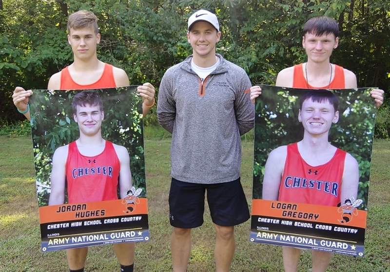 The 2020 CHS senior boys cross country runners, Jordan Hughes (left) and Logan Gregory (right) with coach Chris Kern. The boys are holding the senior banners presented to them by Sgt. Dane Patterson of the Illinois National Guard.