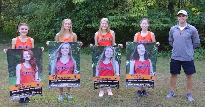 The 2020 Lady Jacket senior cross country runners with the banners that were presented to them by Sgt. Dane Patterson of the Illinois National Guard. Left to right: Amelia Shemonic, Josie Kattenbraker, Katie Shinabarger, and Melody Colonel. At right is Chris Kern, head coach.