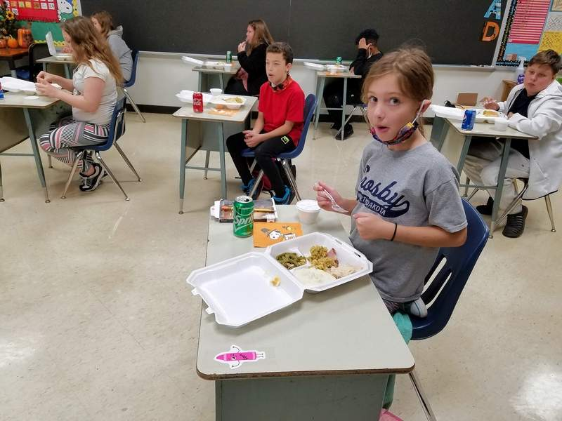 Fifth-grader Laken Garbel enjoys her Thanksgiving dinner with her classmates.