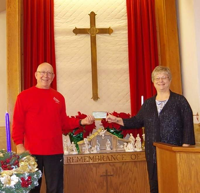 Methodist Men President Jim Beers, presents Patti Nanney with a check to pay for shipping the 25 shoe box gifts.