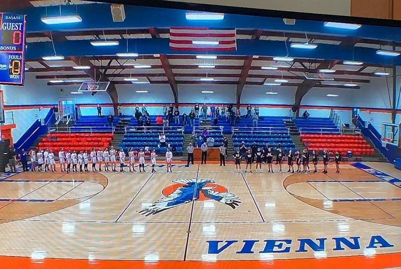 The varsity Lady Jackets and Lady Eagles stand for pre-game ceremonies at the 2021 season opener on Saturday.