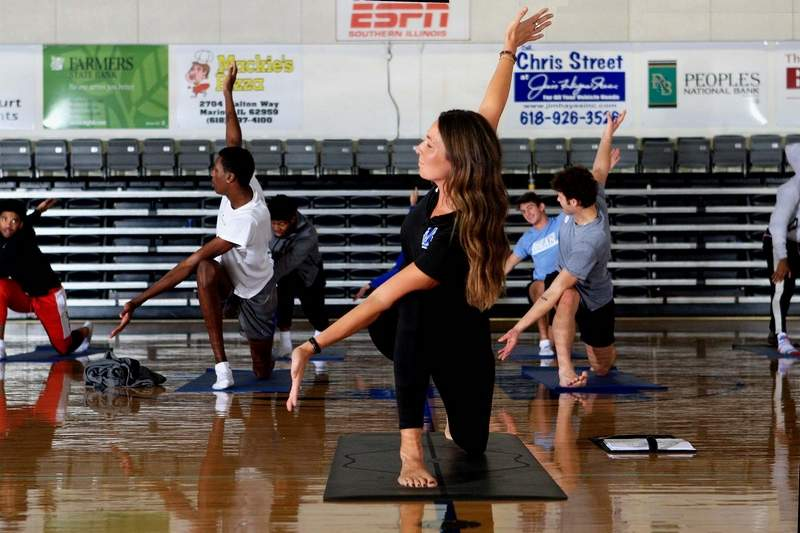 Marion native and John A. Logan women's golf coach Lauren Bond-Clark leads the Volunteer men's basketball team through a yoga workout session. The nation's No. 4 ranked NJCAA DI team has embraced the physical, mental and spiritual practice of yoga and is feeling good doing so.