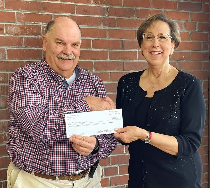 Mardell Granger, Memorial Hospital Auxiliary president, gives a $9,000 check to Tom Search, the Memorial Hospital Board chairman.