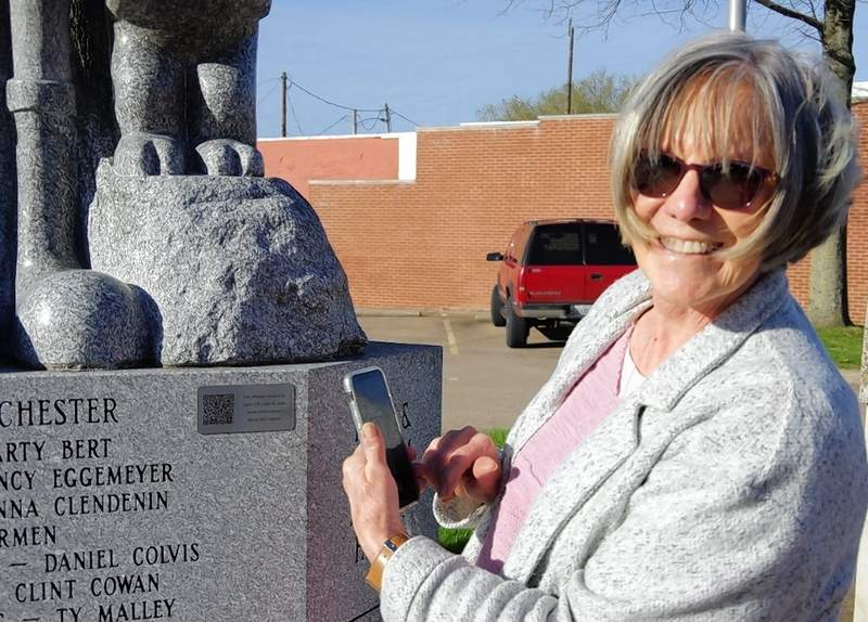 Jim Beers photoBrenda Owen stands with the Olive/Swee'Pea/Jeep statue at the Randolph County Courthouse, pointing to where the QR code has been installed.
