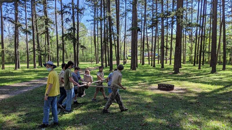 Harrisburg Troop 7023B members carry Peyton Daymon on a self-made transport frame during the pioneering event.
