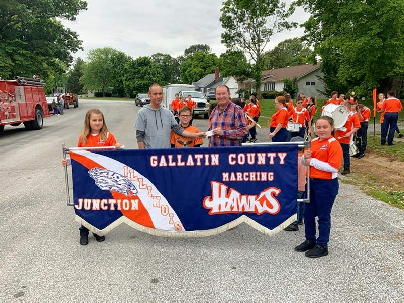 Shawneetown Mayor David Barker, joined by his grandson Brady Barker, delivers a check for $500 to Gallatin County Schools Band Director and music teacher Ben Austin to be used for the Gallatin County Marching Band. The band entertained the crowds at Coal Days festivities, Barker said.