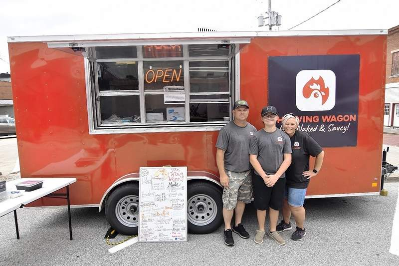 From left, Dustin, Triton and Tiffany Kielhorn stand by The Wing Wagon Saturday outside Southern Illinois Axe & Ale's tap room.