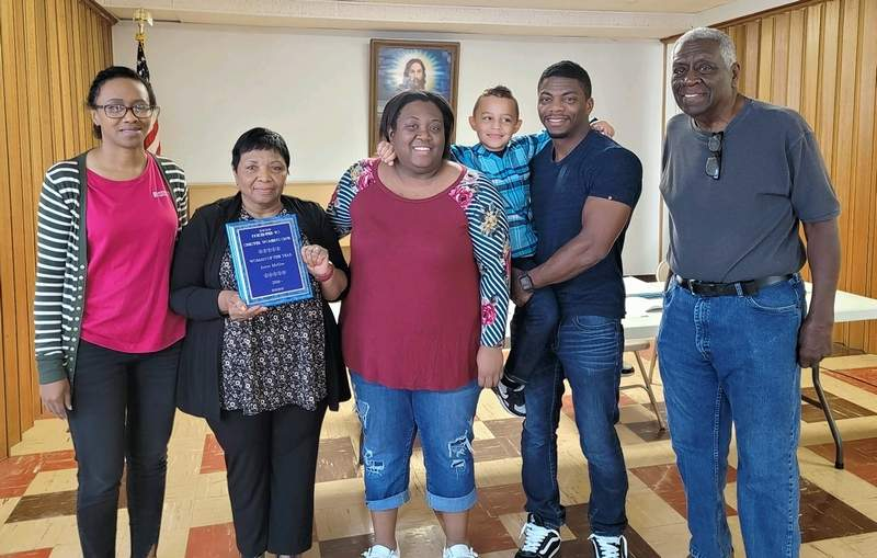 Joyce McGee, with plaque, is named Woman of the Year by the Chester Women's Club on Sept. 24. Surprising her at the presentation were members of her family. From left are her daughter Mecca Korando, Joyce McGee, daughter Allyson McGee, grandson Lawson McGee, son Collin McGee and Joyce's husband, Walter McGee.