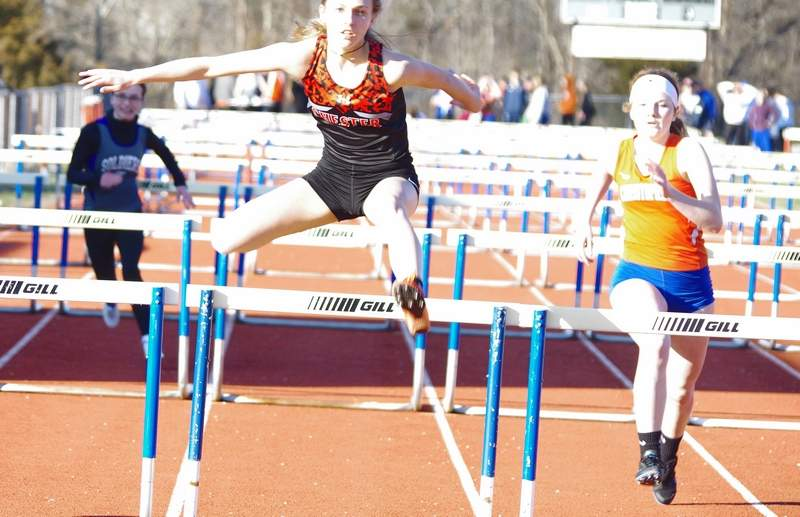 Lady Jacket sophomore Josie Kattenbraker, center, clears the final hurdle en route to her victory in the 100-meter hurdle event on March 21.
